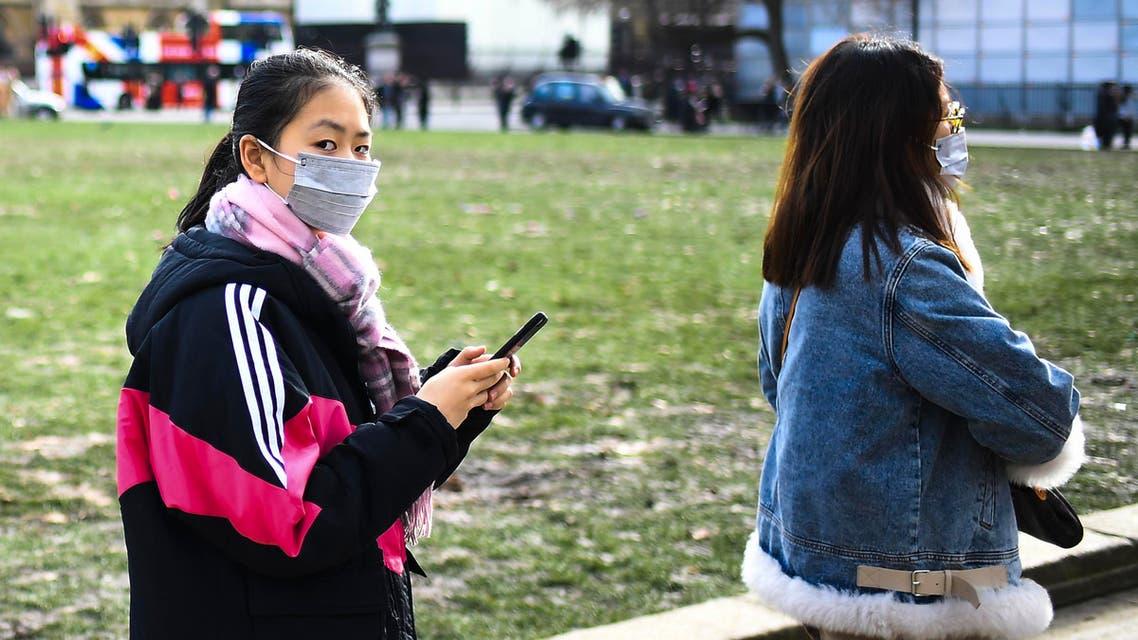 Two women in masks walk in Parliament Square, in London, Saturday, Feb. 1, 2020. (AP)