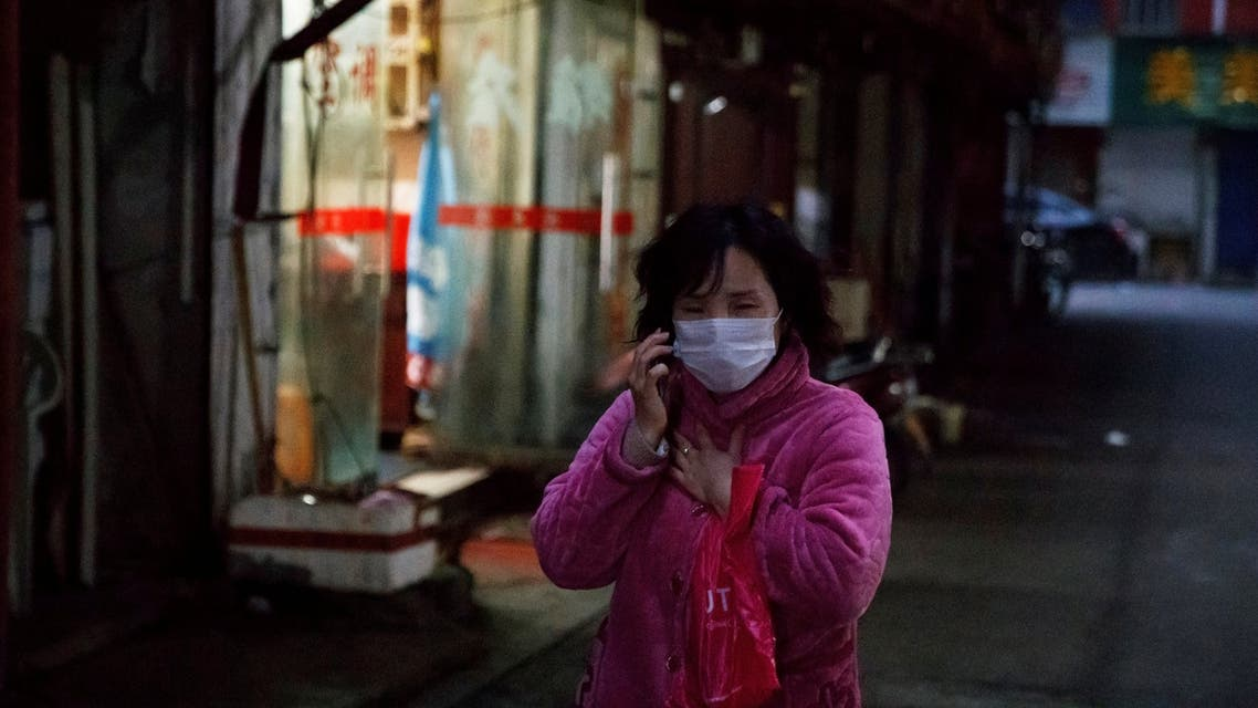 A woman wears a face mask in a market alley in Jiujiang, Jiangxi province, China, as the country is hit by an outbreak of a new coronavirus, February 1, 2020. REUTERS/Thomas Peter