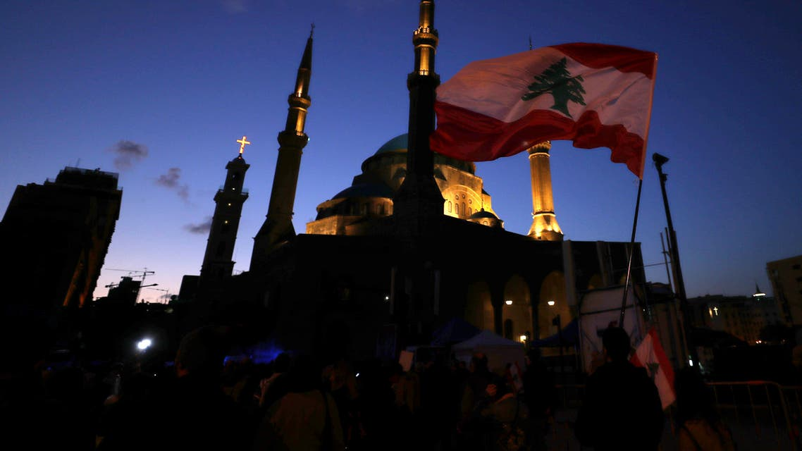 Anti-government protesters wave Lebanese flags and chant slogans, during ongoing protests against the Lebanese government, in Beirut, Lebanon, Saturday, Feb. 1, 2020.(AP Photo/Hassan Ammar)