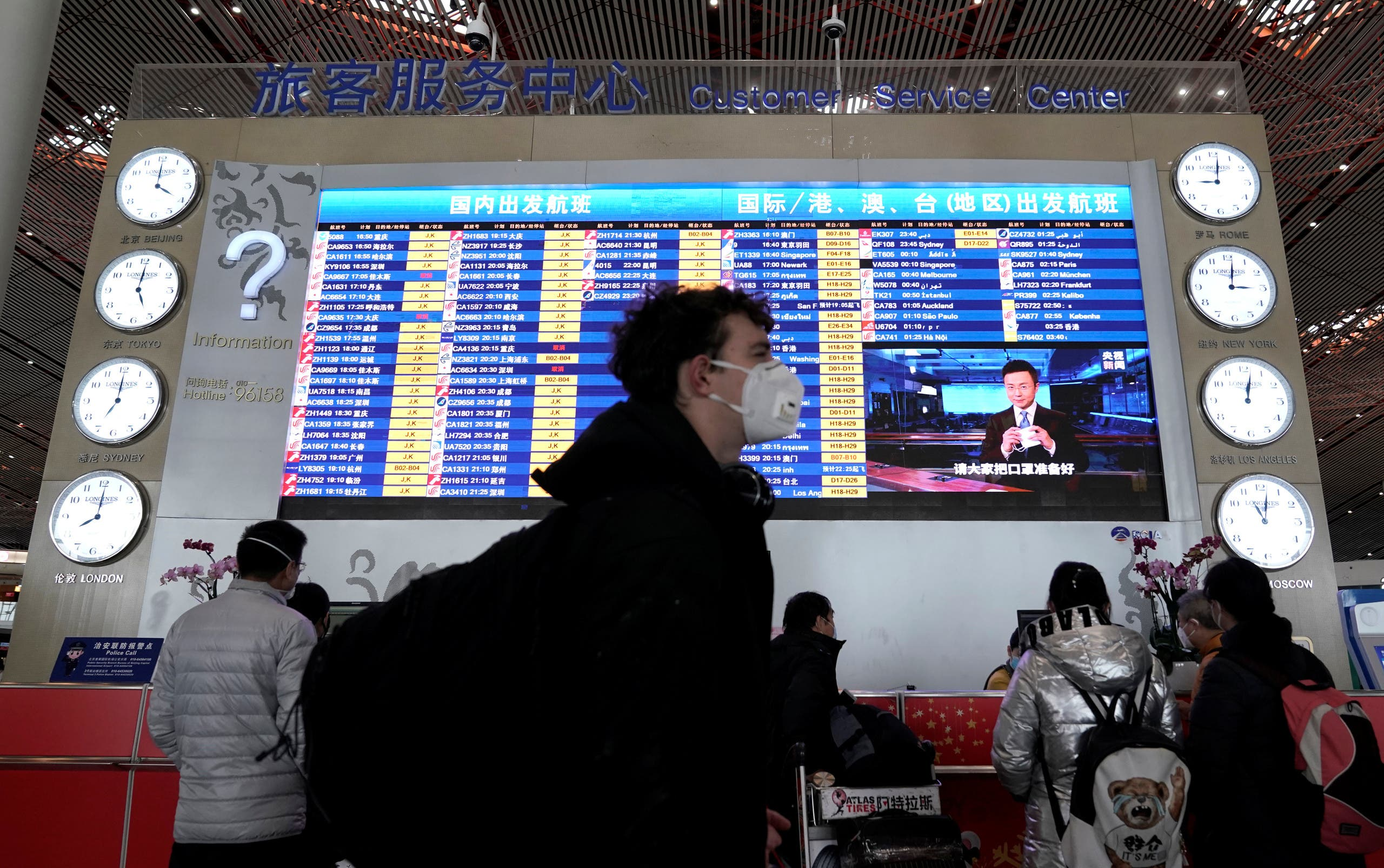 A foreign traveller wearing a mask walks past a departures information board at Beijing International Airport in Beijing, China as the country is hit by an outbreak of the new coronavirus, February 1, 2020. (Reuters)