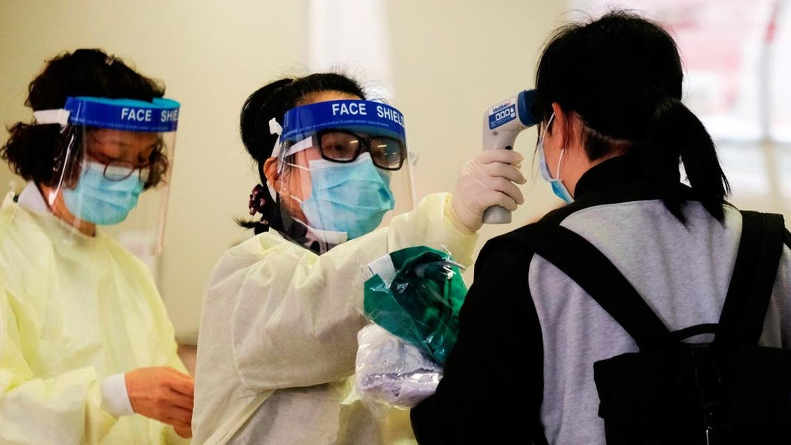 A medical worker takes the temperature of a woman in the reception of Queen Elizabeth Hospital, following the outbreak of a new coronavirus, in Hong Kong, China February 3, 2020. (File photo: Reuters)