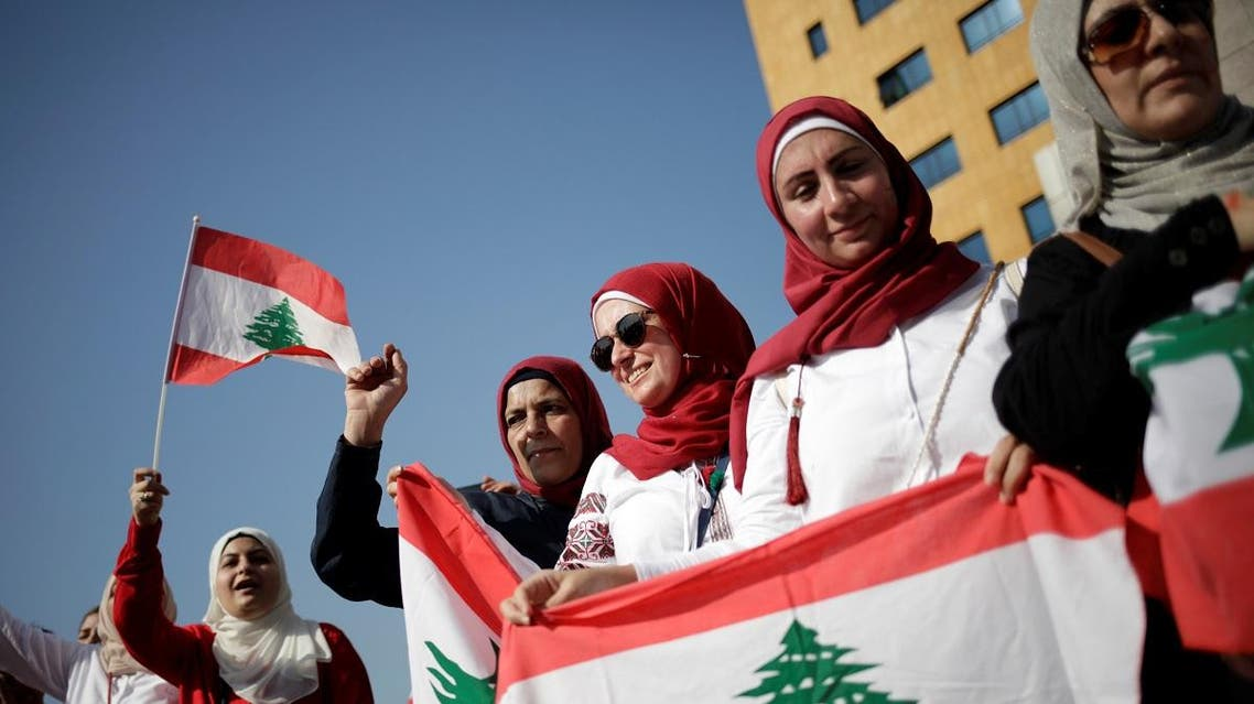 Women carry national flags during ongoing anti-government protests near the Ministry of Education and Higher Education in Beirut, Lebanon November 7, 2019. REUTERS