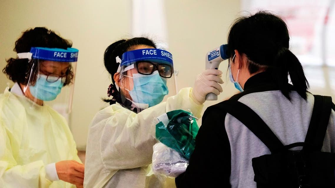 A medical worker takes the temperature of a woman in the reception of Queen Elizabeth Hospital, following the outbreak of a new coronavirus, in Hong Kong. (Reuters)