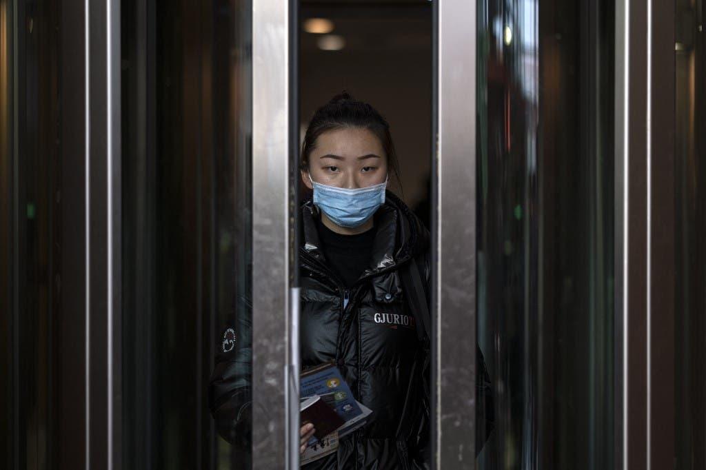 مسافرة صينية تضع القناع الطبي في مطار بالمكسيك