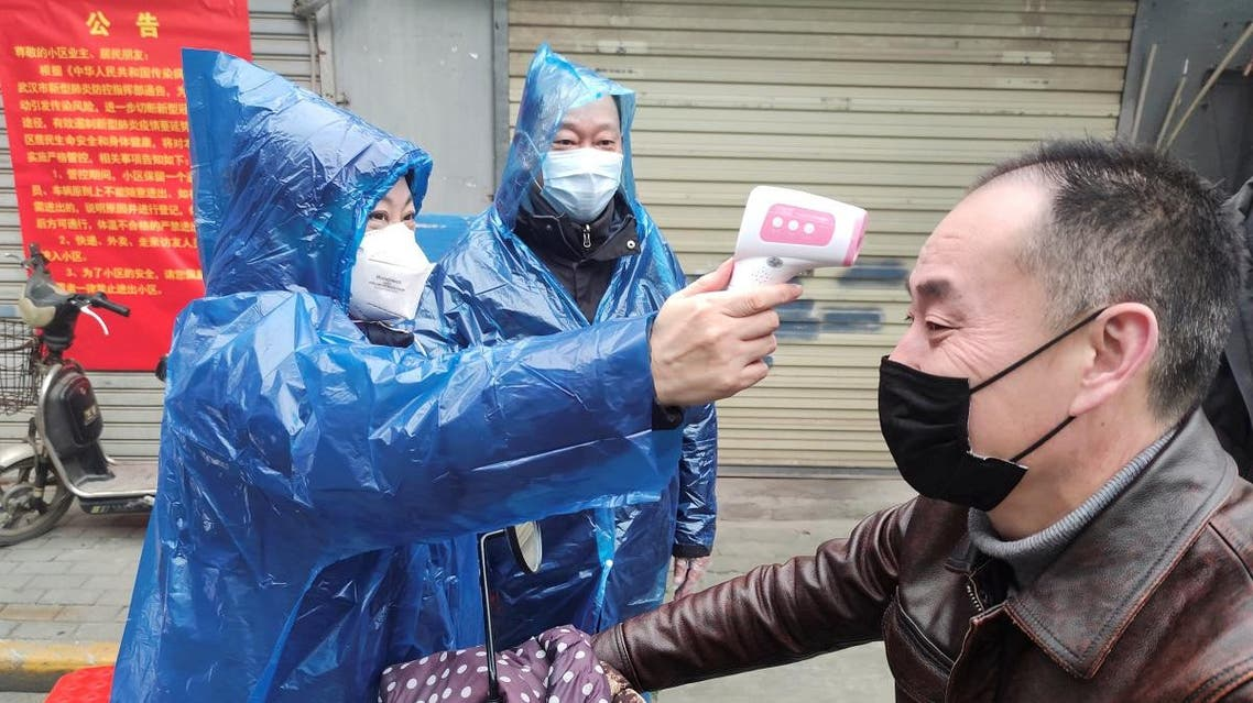 Worker takes body temperature measurement of a man at the entrance to a residential compound following an outbreak of the new coronavirus in Wuhan. (Reuters)