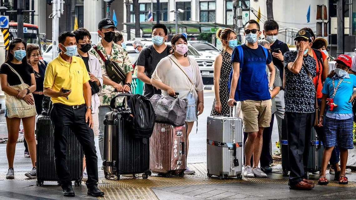 People with protective facemasks wait at a crossroad in downtown Bangkok on February 3, 2020. (Photo: AFP)