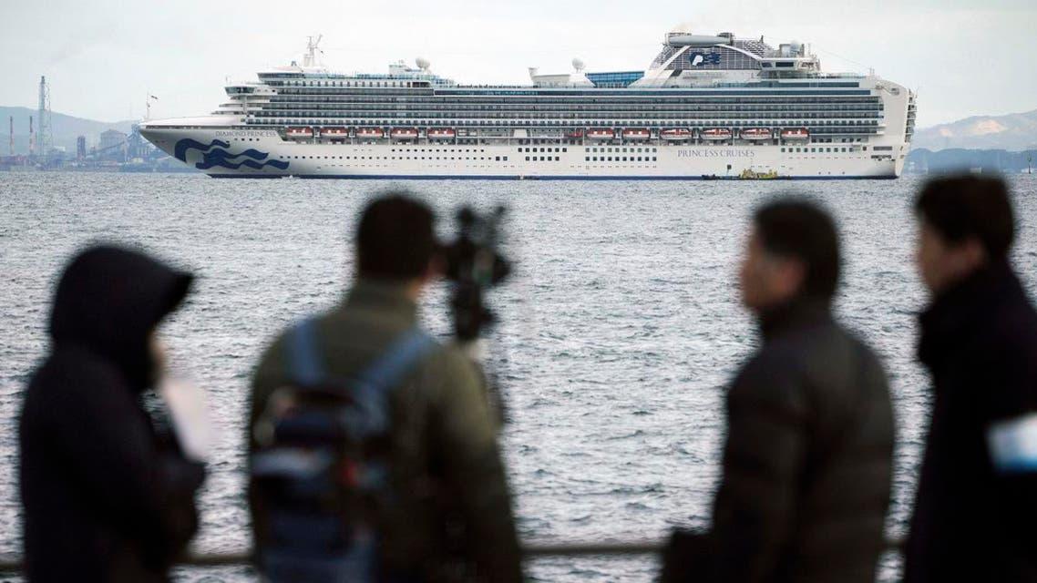 A TV crew film a cruise ship Diamond Princess anchoring off the Yokohama Port on February 4, 2020, in Yokohama, near Tokyo. (AP)
