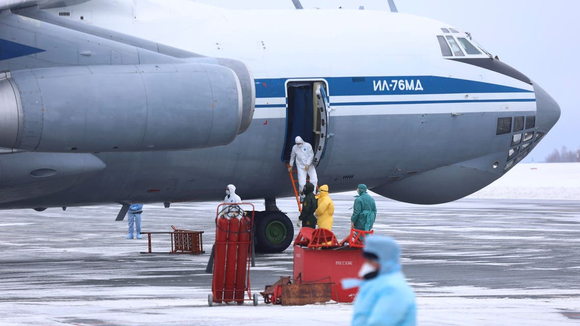 A group of medical personnel prepare to guide 80 people, accompanied by medical specialists, carried by a Russian military plane at an airport outside Tyumen, Russia. (AP)