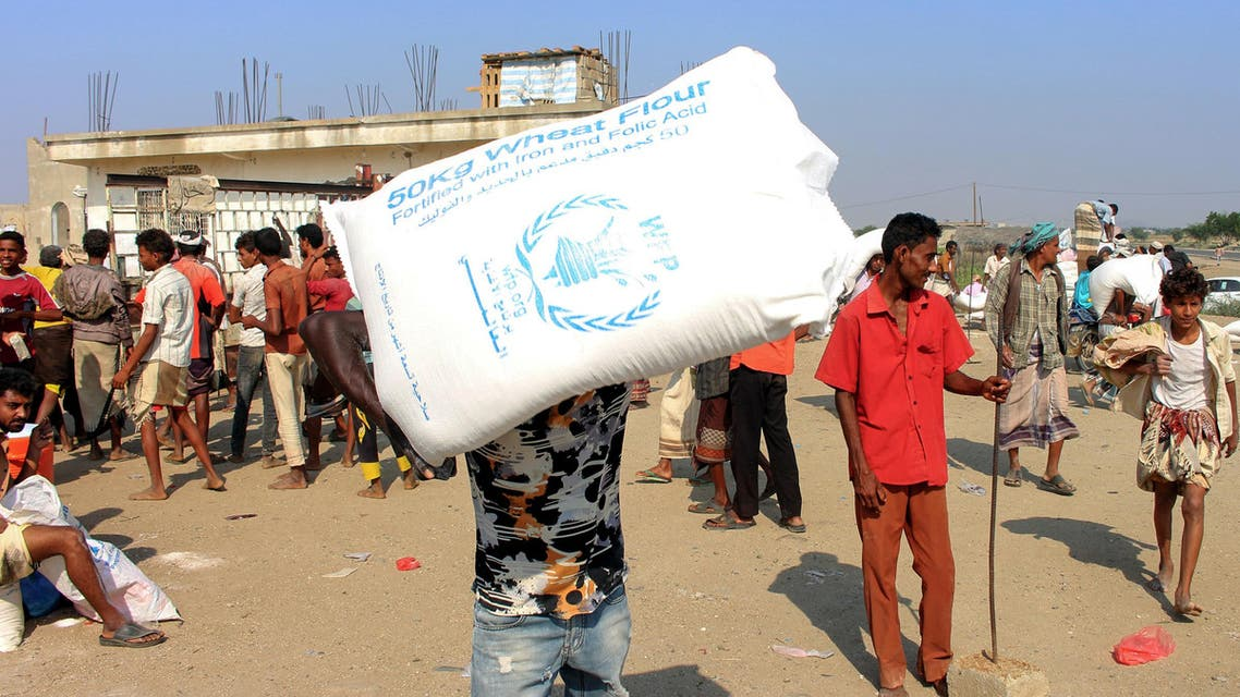 Displaced Yemenis receive humanitarian aid donated by the World Food Programme in cooperation with the Danish Refugee Council. (File photo: AFP)