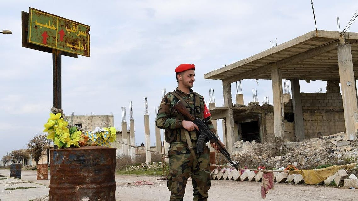 "A Syrian Army soldier stands guard next to a street sign reading ""Saraqeb"" in Tall Sultan town, in Syria's northwestern Idlib province on February 5, 2020. (AFP)"
