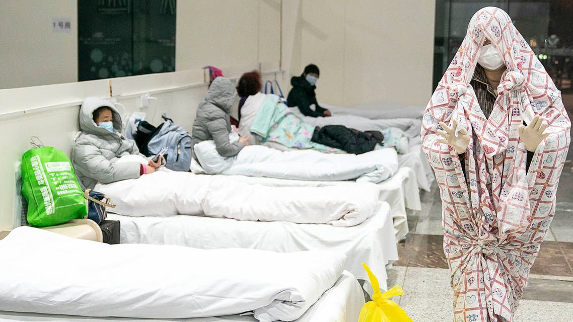 This photo taken on February 5, 2020 shows a patient (R) covered with a bed sheet at an exhibition centre converted into a hospital as it starts to accept patients displaying mild symptoms of the novel coronavirus in Wuhan in China's central Hubei province. China scrambled to find bed space for thousands of newly infected patients on February 6, as the toll from a deadly new virus jumped again with more than 28,000 people known infected nationwide and 563 deaths.