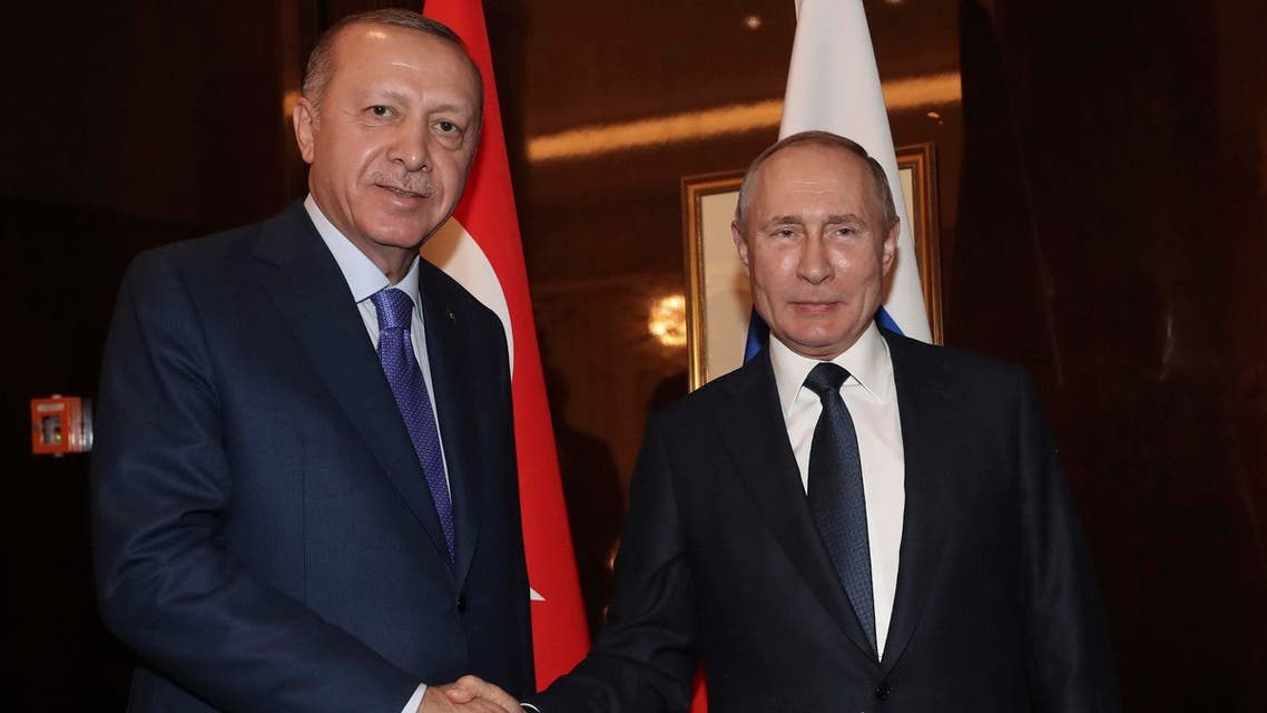 Russian President Vladimir Putin, right, shakes hands with Turkish President Recep Tayyip Erdogan on the sideline of the conference on Libya. (AP)