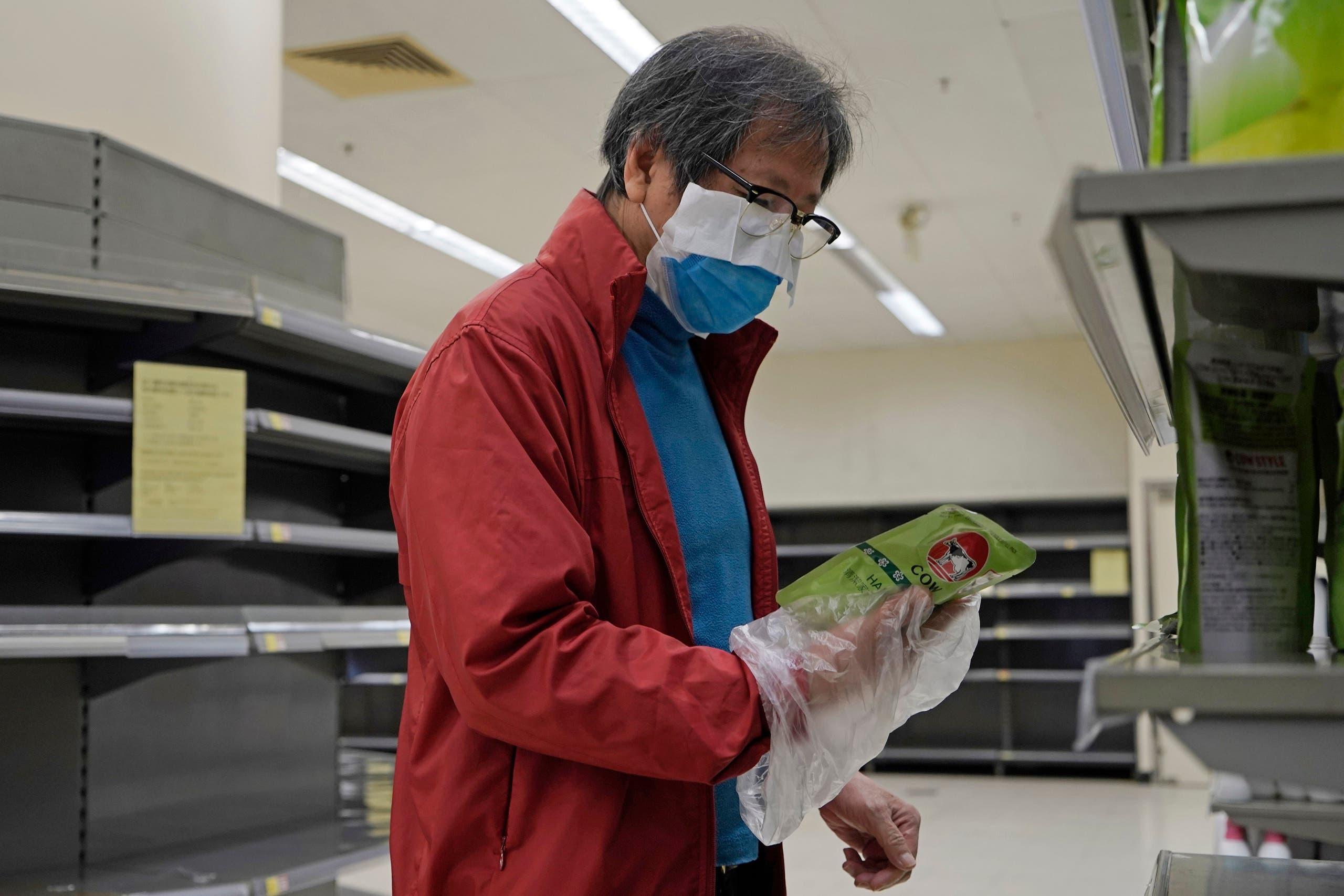 رجل يرتدي قناع طبي وكيس من البلاستيك وهو يعاين أحد المنتجات في سوبر ماركت بهونغ كونغ