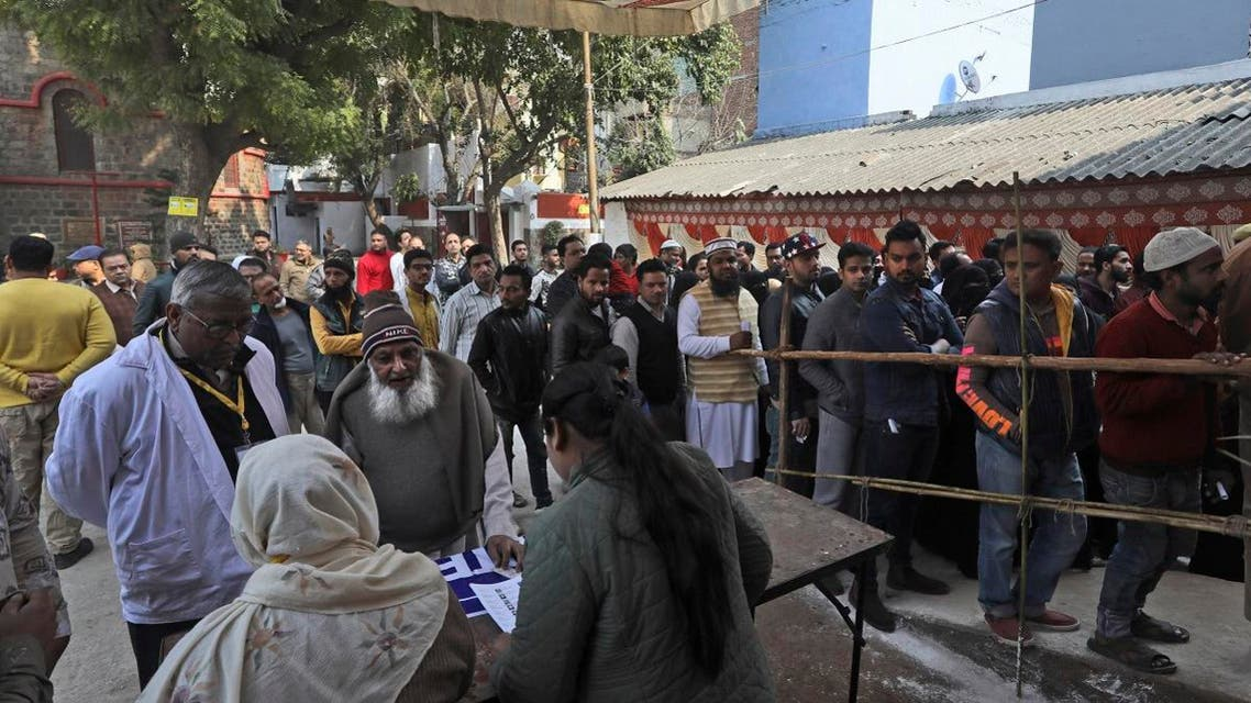 Indian Muslims look for their names in the voters' list at a polling station inside a Church complex in New Delhi, India, Saturday, Feb. 8, 2020. (AP)