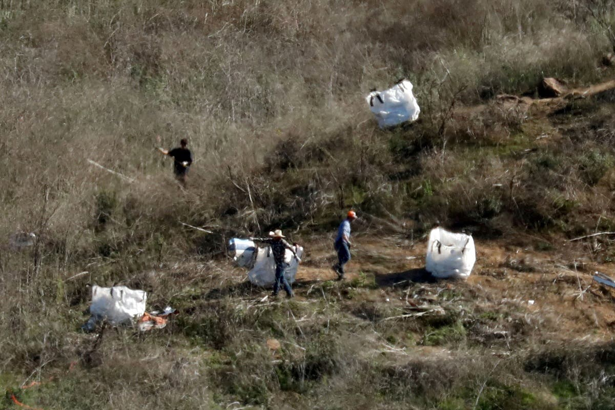 Personnel collect debris while working with investigators at the helicopter crash site of NBA star Kobe Bryant in Calabasas, California. (File photo: Reuters)