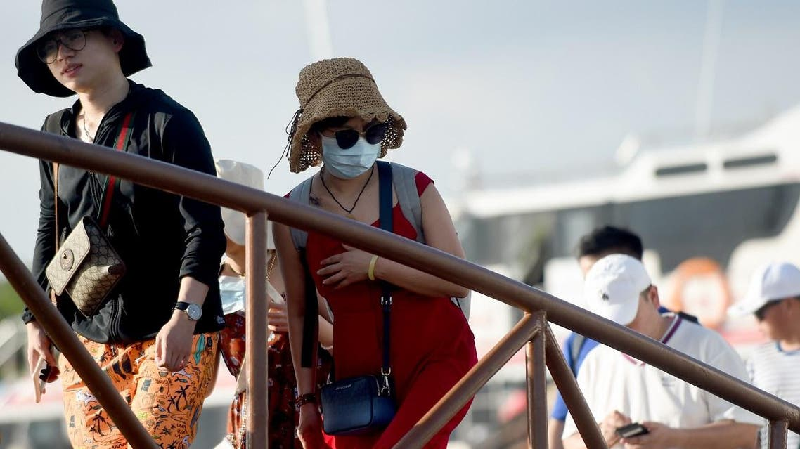 A Chinese tourist (C) wearing a facemask as a preventative measure following a coronavirus outbreak which began in the Chinese city of Wuhan, arrives with others from Nusa Penida at the fast boat pier in Serangan island in Denpasar, on Indonesia's resort island of Bali on January 27, 2020. (AFP)