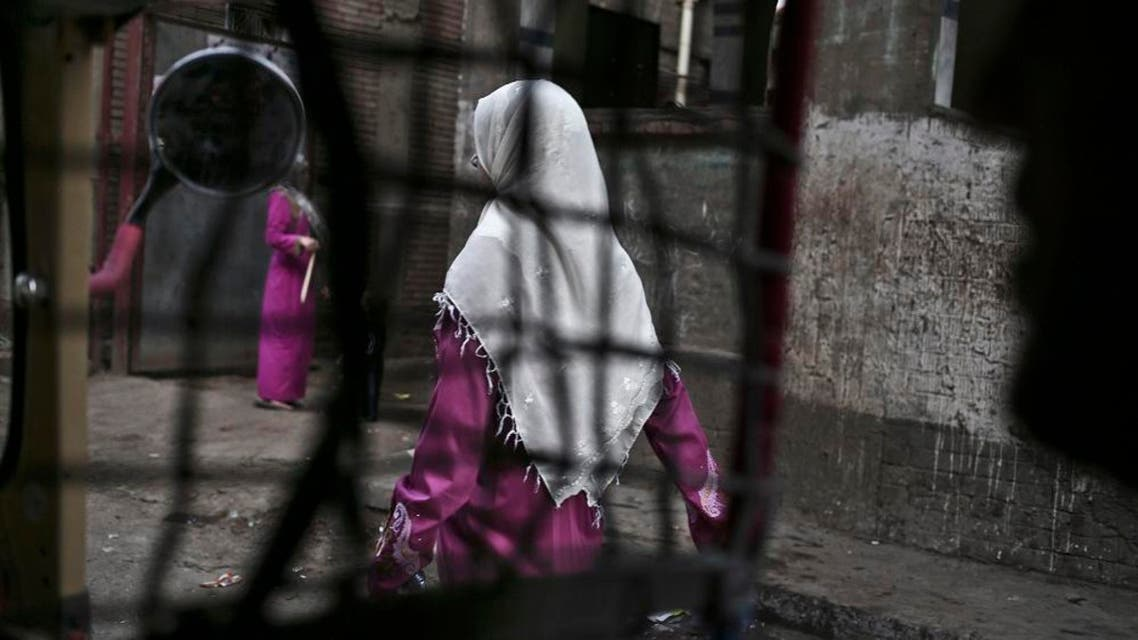 an Egyptian woman seen from a motorized rickshaw walks on a street, near the home of 13-year-old Sohair el-Batea who died undergoing the procedure of female genital mutilation committed by Dr. Raslan Fadl, in Dierb Biqtaris village, on th AP