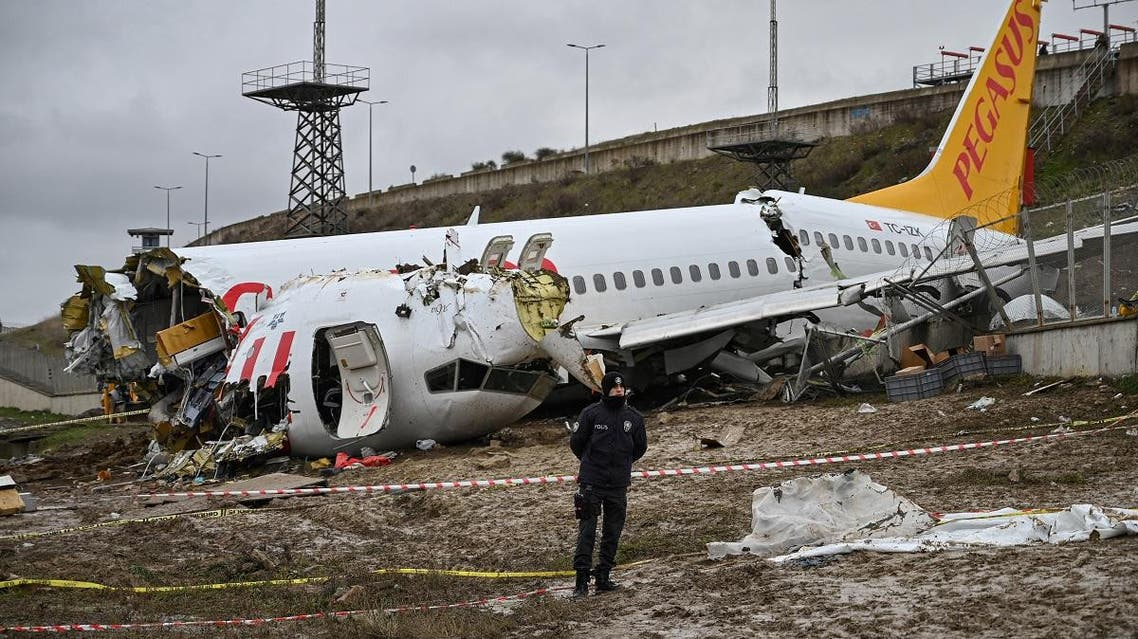 A Turkish police officer stands guard on site of a plane accident and in front of the wreckage of Pegasus Airlines Boeing 737 airplane that skidded off the runway upon landing at the Sabiha Gokcen airport, in Istanbul, on February 6, 2020. (AFP)