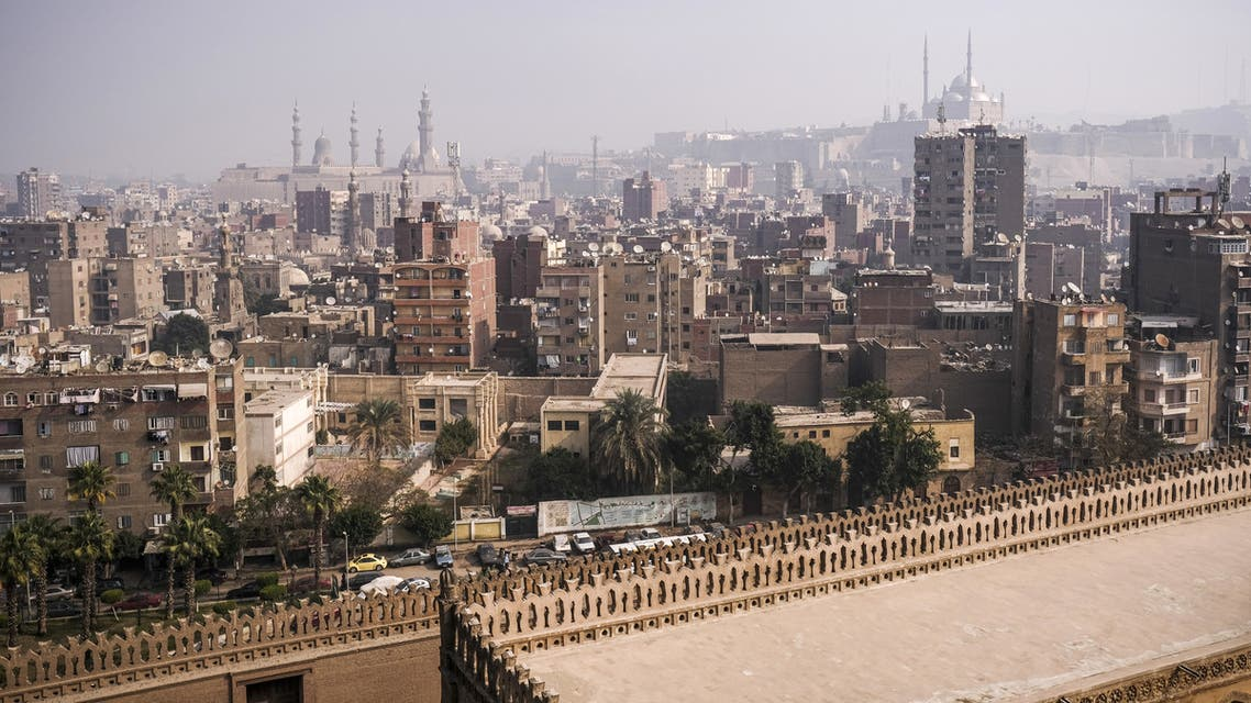 This picture taken on January 11, 2020 from the minaret of the ninth century mosque of Ibn Tulun shows a view of the mosque's roof and a backdrop of the Egyptian capital Cairo, with the 19th century Grand Mosque of Mohamed Ali Pasha (R) situated in the Cairo Citadel and the minarets of the 20th and 14th century mosques of al-Rifai and Sultan Hassan seen in the background (L).