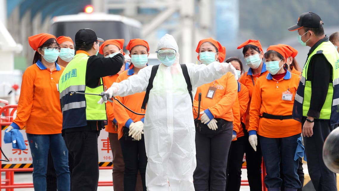 An epidemic prevention worker in a protective suit stands by to get on board the cruise ship SuperStar Aquarius docked at Keelung port in New Taipei City. (AP)