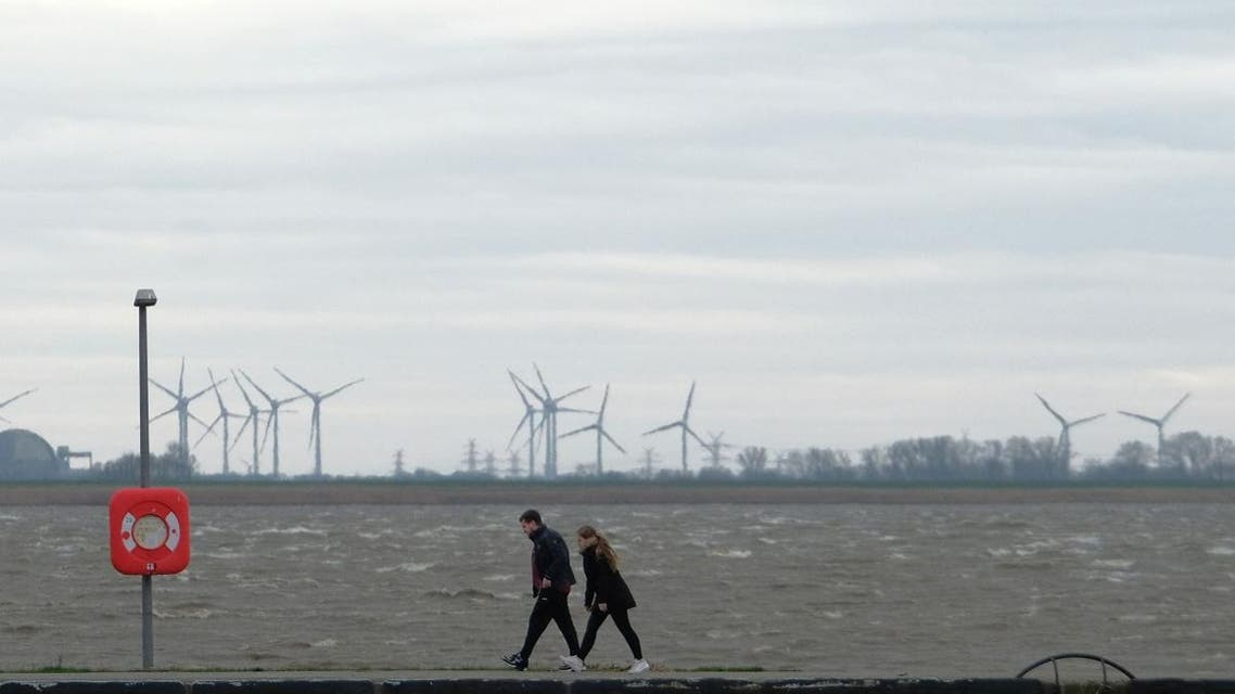 People walk along a seawall at the North Sea in Bremerhaven, northern Germany, on Febuary 9, 2020. (AFP)