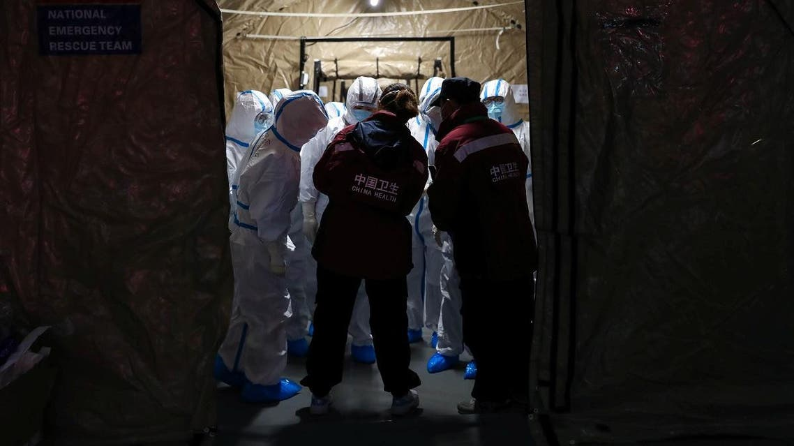 Medical workers in protective suits are seen at the Wuhan Parlor Convention Center, which has been converted into a makeshift hospital, in Wuhan. (Reuters)