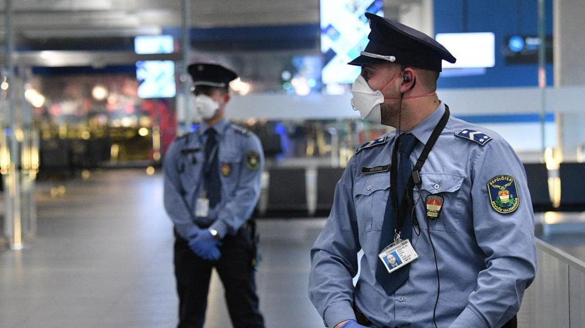 Police oficers wearing protective face masks stand on guard in the hall of Budapest's Liszt Ferenc Airport of on February 5, 2020. (AFP)