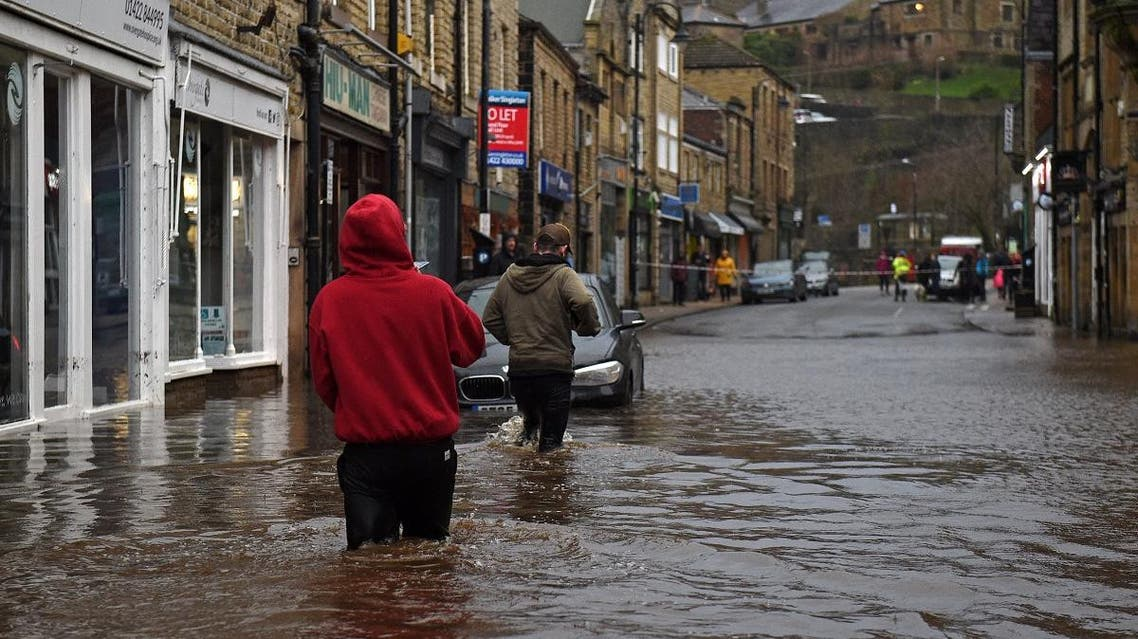 People wade through floodwater in the streets of Hebden Bridge, northern England, on February 9, 2020, as Storm Ciara swept over the country. (AFP)