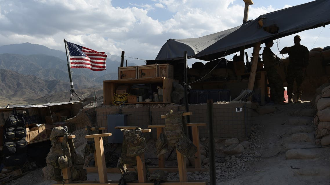 (FILES) In this file photograph taken on July 7, 2018, US Army soldiers from NATO look on as U.S. flag flies at a checkpoint during a patrol against Islamic State militants at the Deh Bala district in the eastern province of Nangarhar Province. Two American troops were killed and six others wounded when an Afghan soldier armed with a machine gun opened fire, the US military confirmed on February 9.