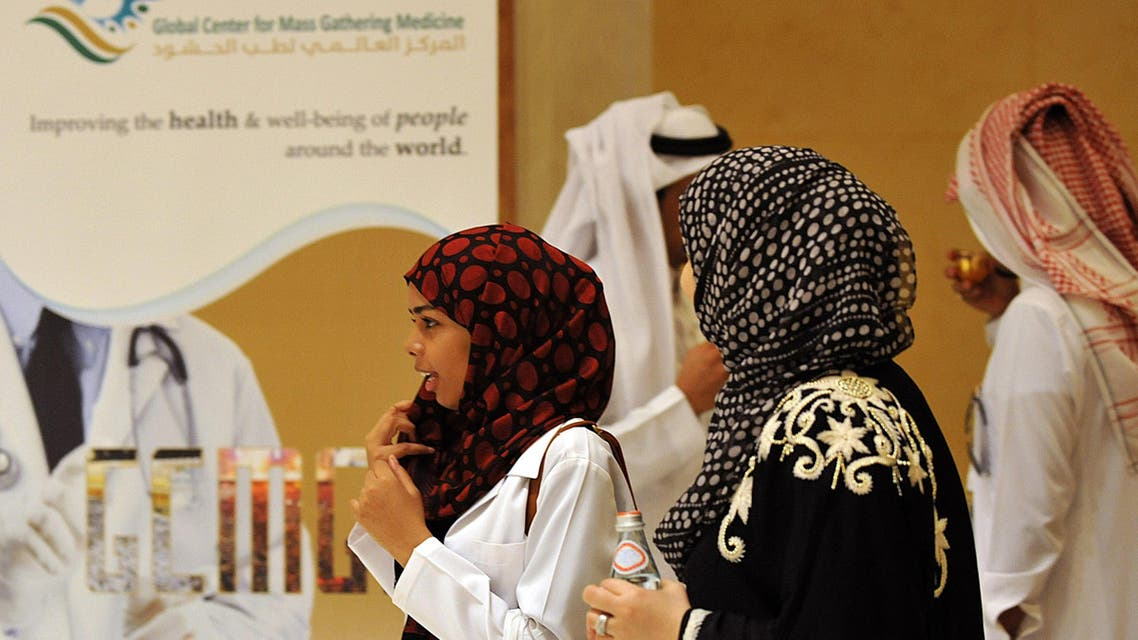 Saudi medical staff pass by a board announcing a three-day-international conference on mass gathering medicine on September 21, 2013 in Riyadh. (AP)