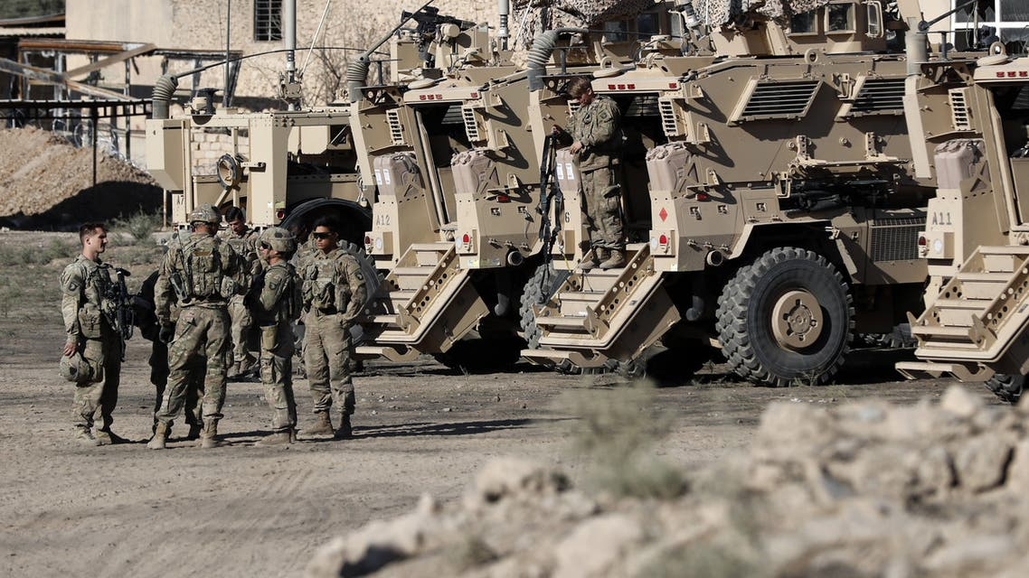US soldiers are seen next to their armoured vehicles near an Iraqi army base on the outskirts of Mosul, on November 23, 2016.