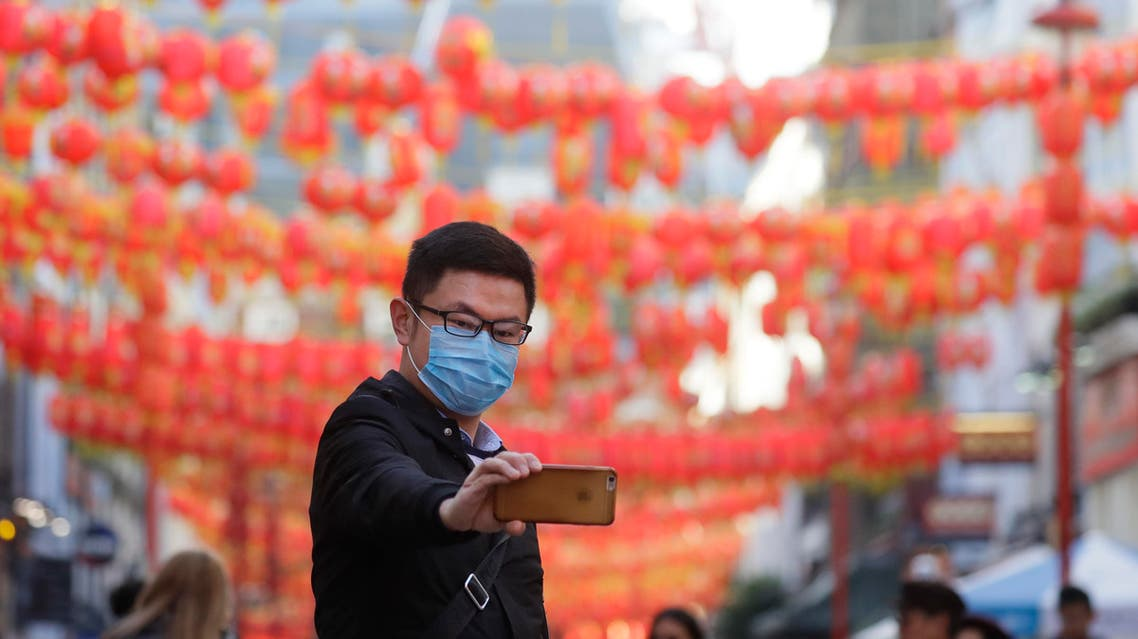 A man wears a mask as he takes a photograph in China Town in London, Friday, Feb. 7, 2020. (AP)