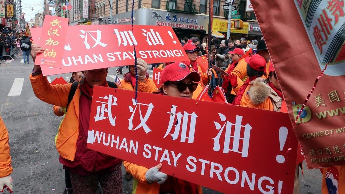 People carry signs in support of Wuhan, China, at the center of the coronavirus outbreak, during the Lunar New Year parade, on February