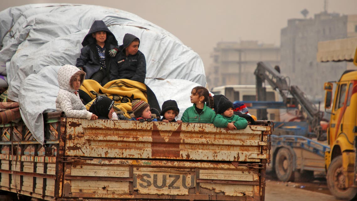 Members of a family fleeing with their belongings pass through the town of Dana in the northern countryside of Syria's Idlib province, on February 5, 2020, on their way northwards toward the Turkish border amid an ongoing regime offensive. A regime offensive in Syria's last rebel enclave has caused one of the biggest waves of displacement in the nine-year war, with tensions spiking between Ankara and Damascus following a deadly exchange of fire.