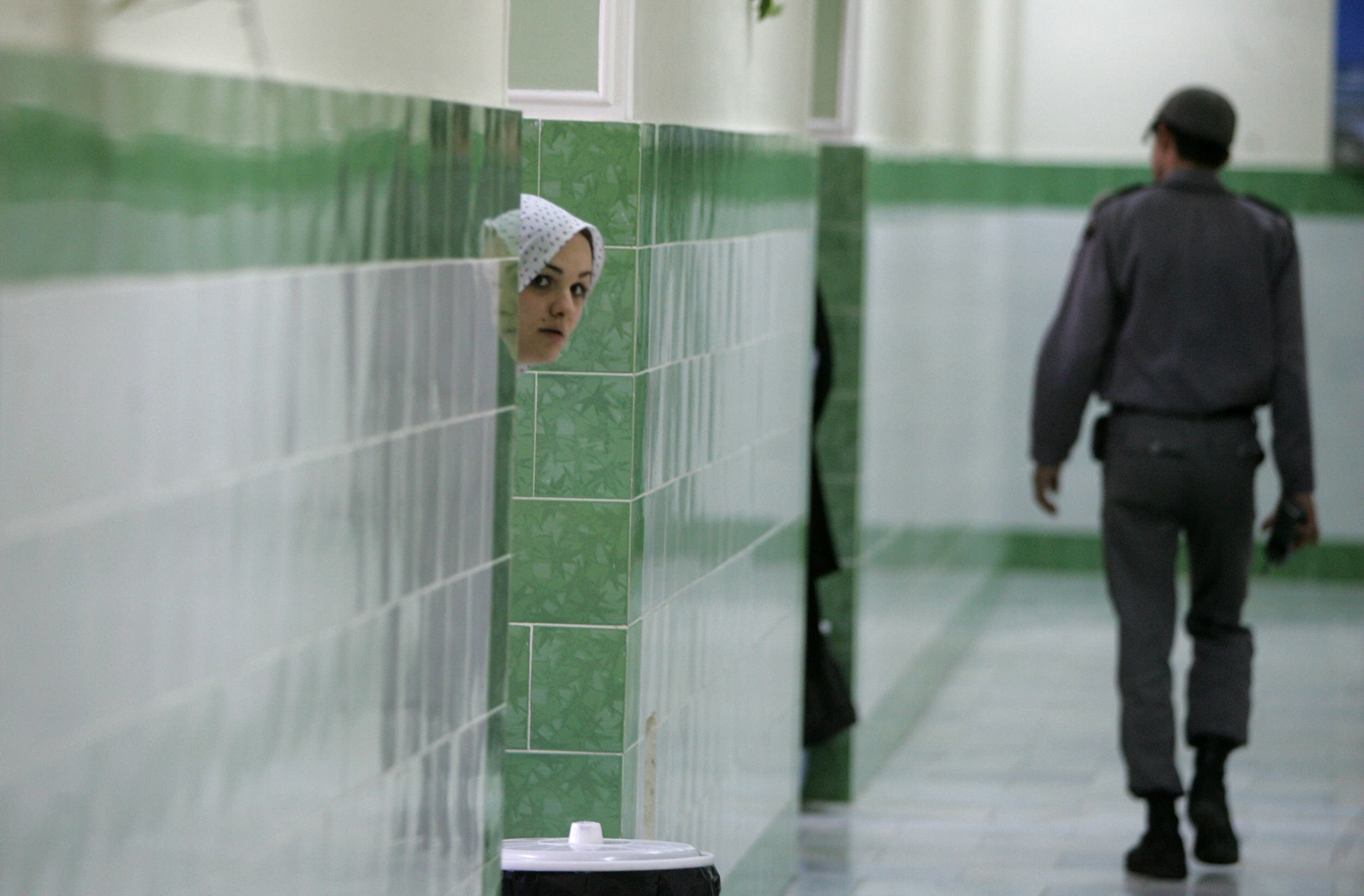 An Iranian inmate peers from behind a wall as a guard walks by at Evin jail, north of Tehran on June 13, 2006. (File photo: AFP)