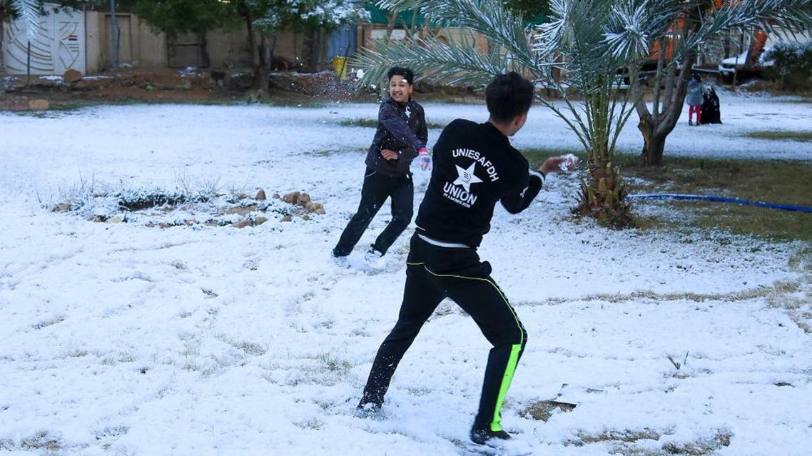 Iraqi boys play with snow in the Shia city of Karbala on February 11, 2020. (AFP)