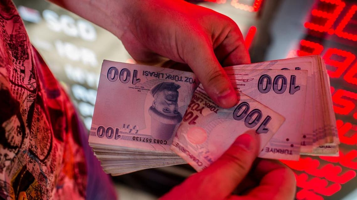 A money changer counts Turkish lira banknotes at a currency exchange office in Istanbul. (AFP)