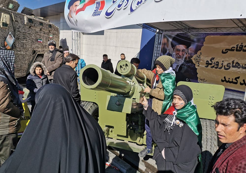 Iranian children pose with howitzer artillery gun during commemorations marking 41 years since the Islamic Revolution. (AFP)