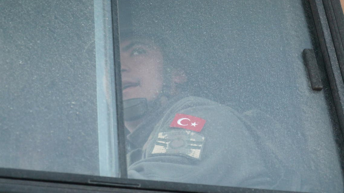 A Turkish military personnel looks out the window of a military vehicle as it enters the Bab al-Hawa crossing at the Syrian-Turkish border, in Idlib governorate, Syria. (Reuters)