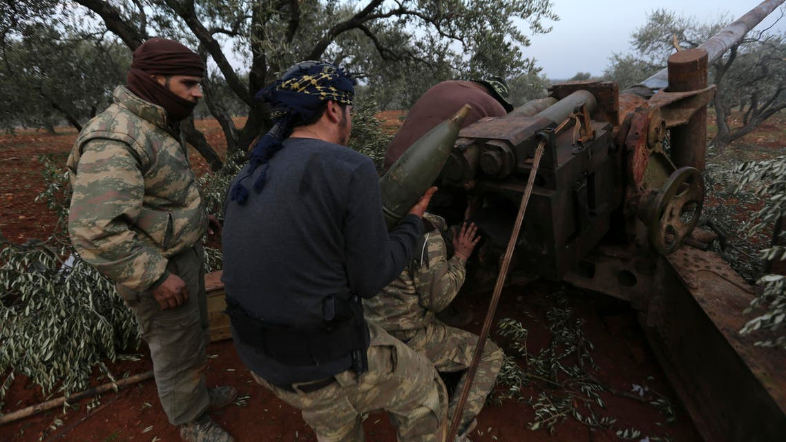 Syrian opposition fighters prepare to shoot a howitzer toward the government positions near the village of Nerab, in Idlib province on Feb. 6, 2020. (AP)