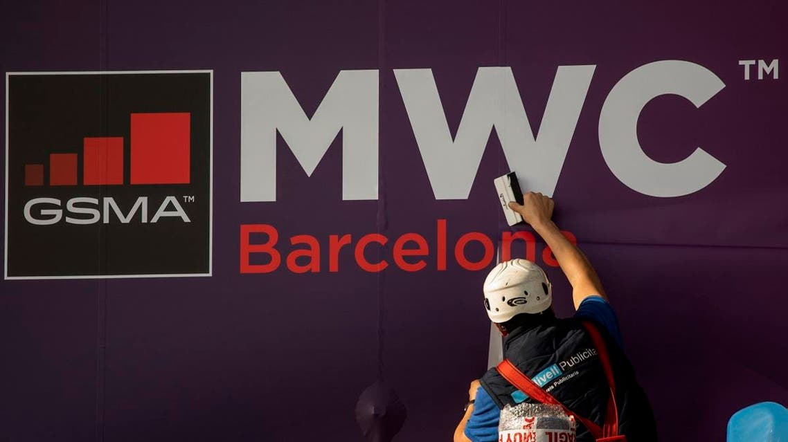 A worker fixes a poster announcing the Mobile World Congress 2020 in a conference venue in Barcelona, Spain. (AP)