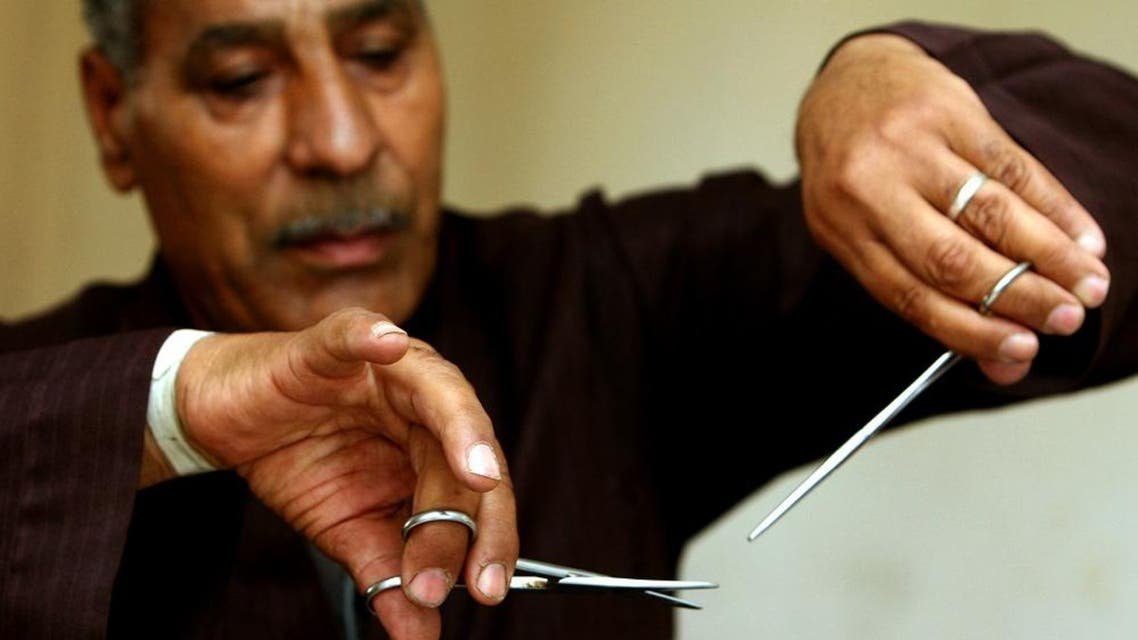 Hassan Hafez, a barber, mimics the way he used to perform female genital mutilation (FGM) in Minia June 13, 2006. (Reuters)