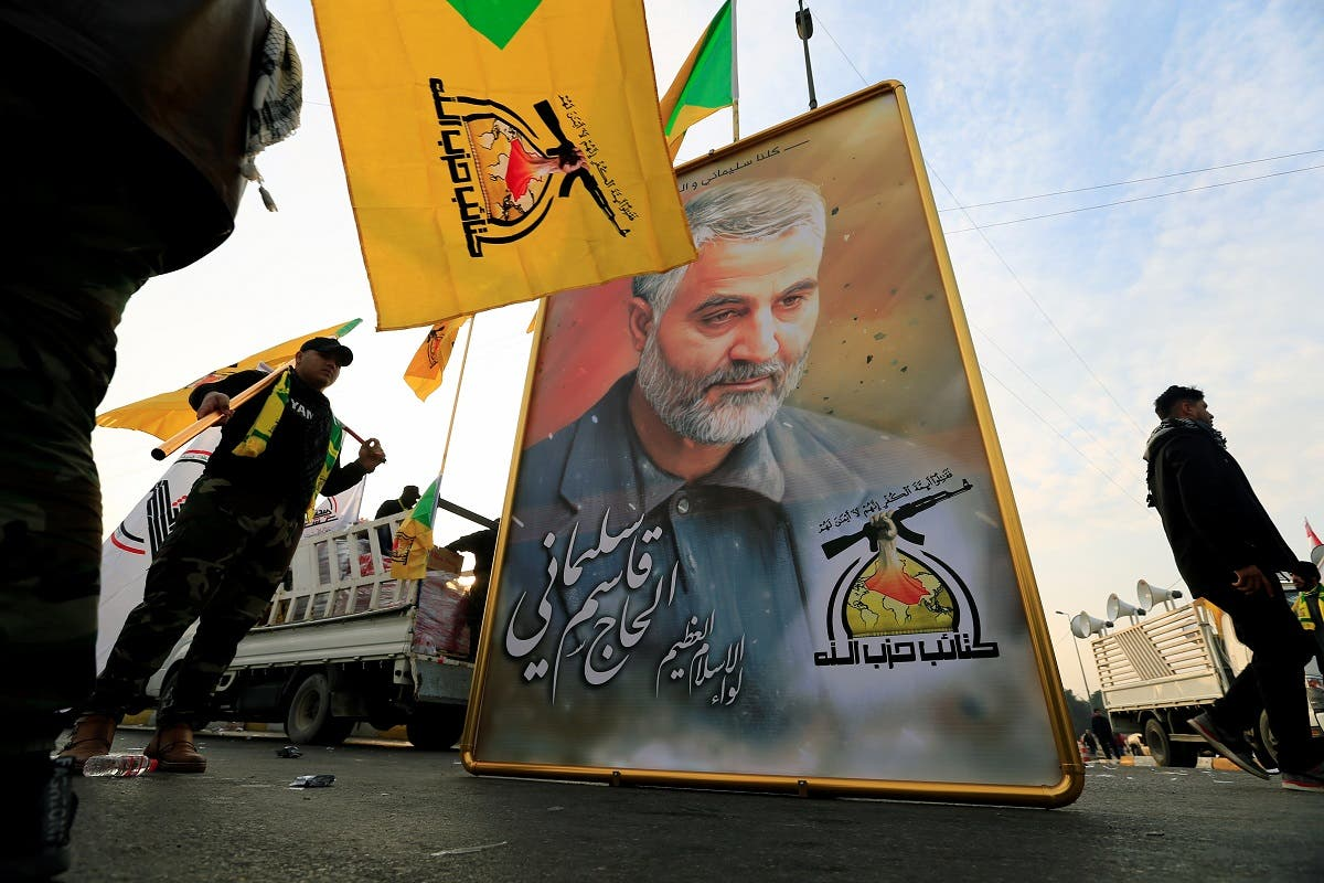 Kataib Hezbollah Iraqi militia hold the picture of the Iranian Major-General Qassem Soleimani, as they gather ahead of the funeral of the Iraqi militia commander Abu Mahdi al-Mohandes, in Baghdad. (Reuters)