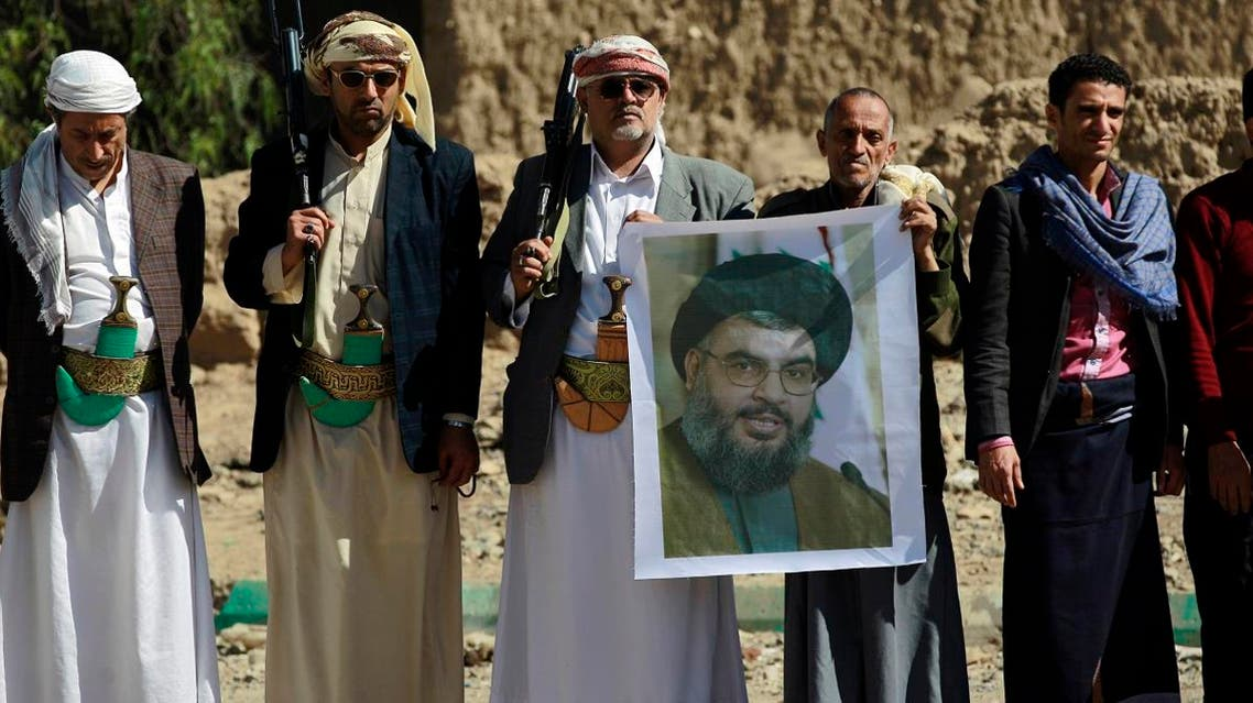 """Huthi militiamen hold posters depicting Lebanon's Hezbollah chief Hassan Nasrallah during a gathering to show their support to Hezbollah following the Gulf states' announcement declaring the group a """" terrorist organization"""", in the capital Sanaa, on March 3, 2016. (AFP)"""