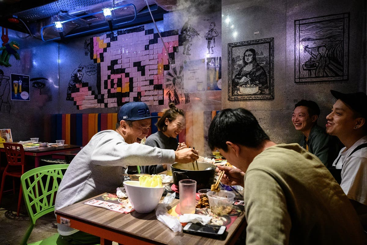 A group of friends share a laugh as they eat together at 66 Hotpot, a family-run restaurant in the bustling district of Mongkok in Hong Kong. (AFP)