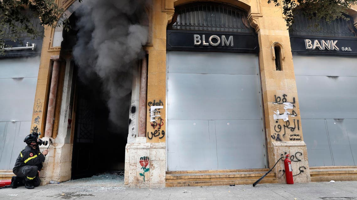 A firefighter looks before entering a bank that was set on fire by anti-government protesters, during a protest in downtown Beirut, Lebanon. (AP)