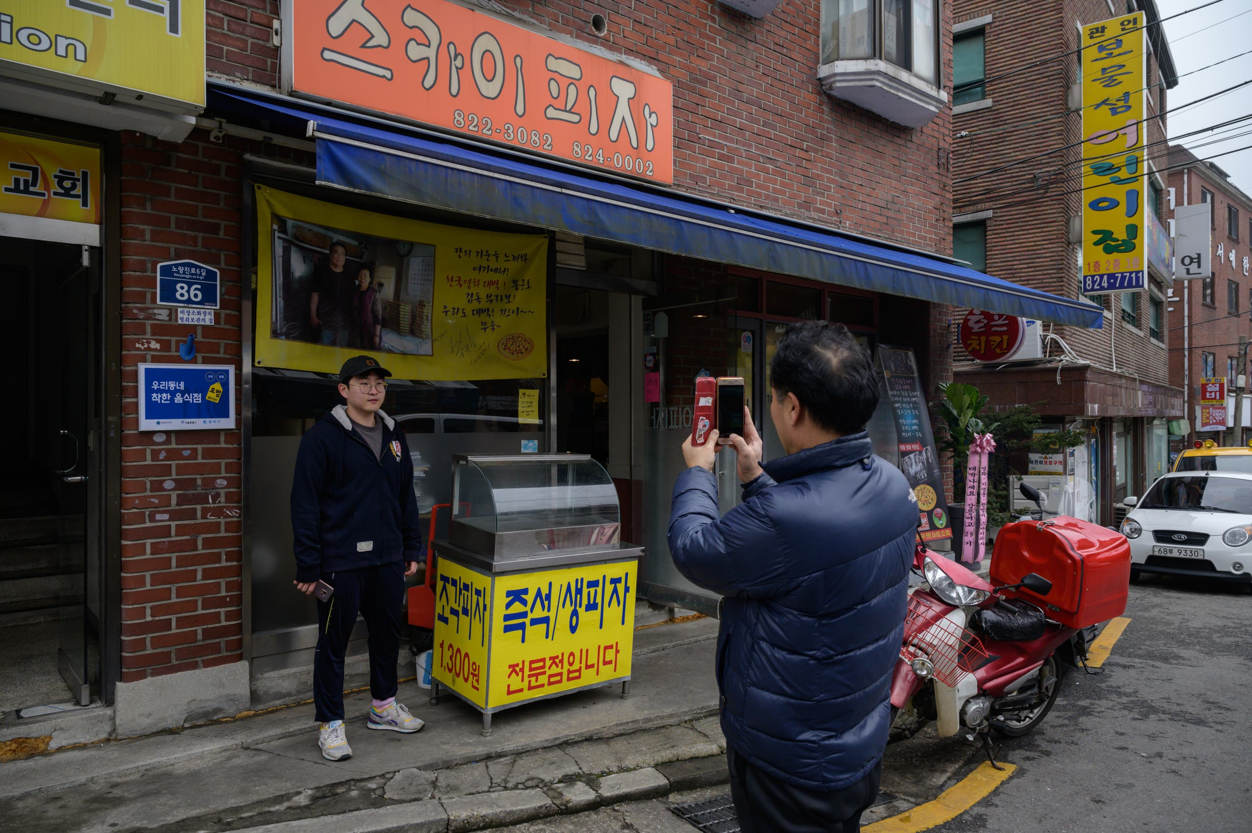 A customer poses before a photo of film director Bong Joon-ho at the 'Sky Pizza' restaurant in Seoul on February 13, 2020. (AFP)
