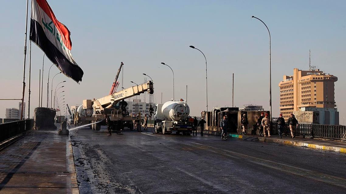 After pushing out anti-government protesters from the area, municipal workers clean while security forces remove concrete walls in preparations to re-open Sinak Bridge. (AP)