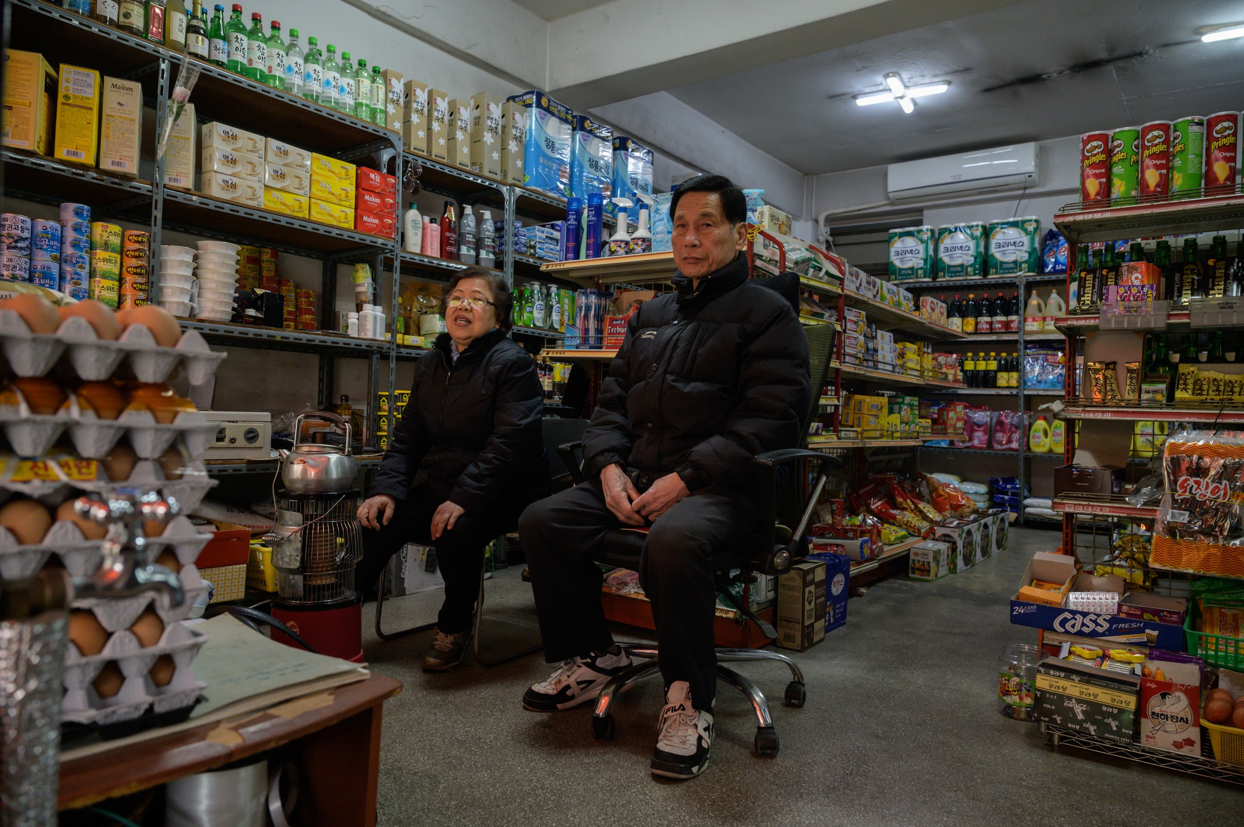Owner Kim Kyung-soon (L) sits in the Pig Rice supermarket in Seoul on February 13, 2020. (AFP)