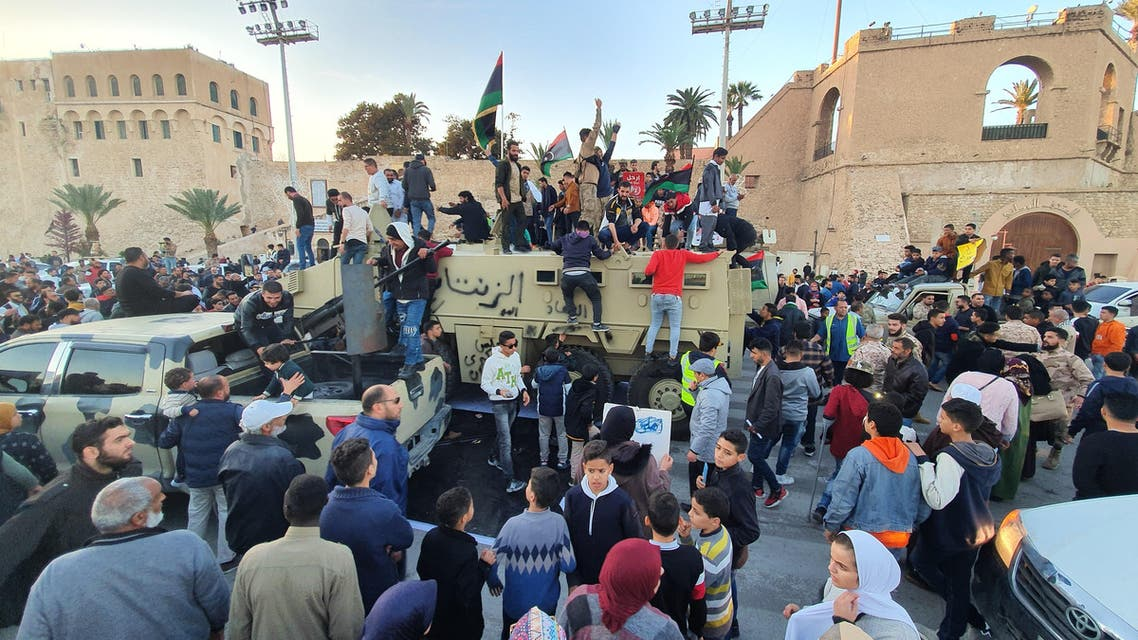 """People stand and sit with Libyan national flags above armoured military vehicles of forces loyal to the UN-recognised Tripoli-based """"Government of National Accord"""" (GNA) during a celebration in the capital's Martyrs' Square on January 31, 2020. (AP)"""
